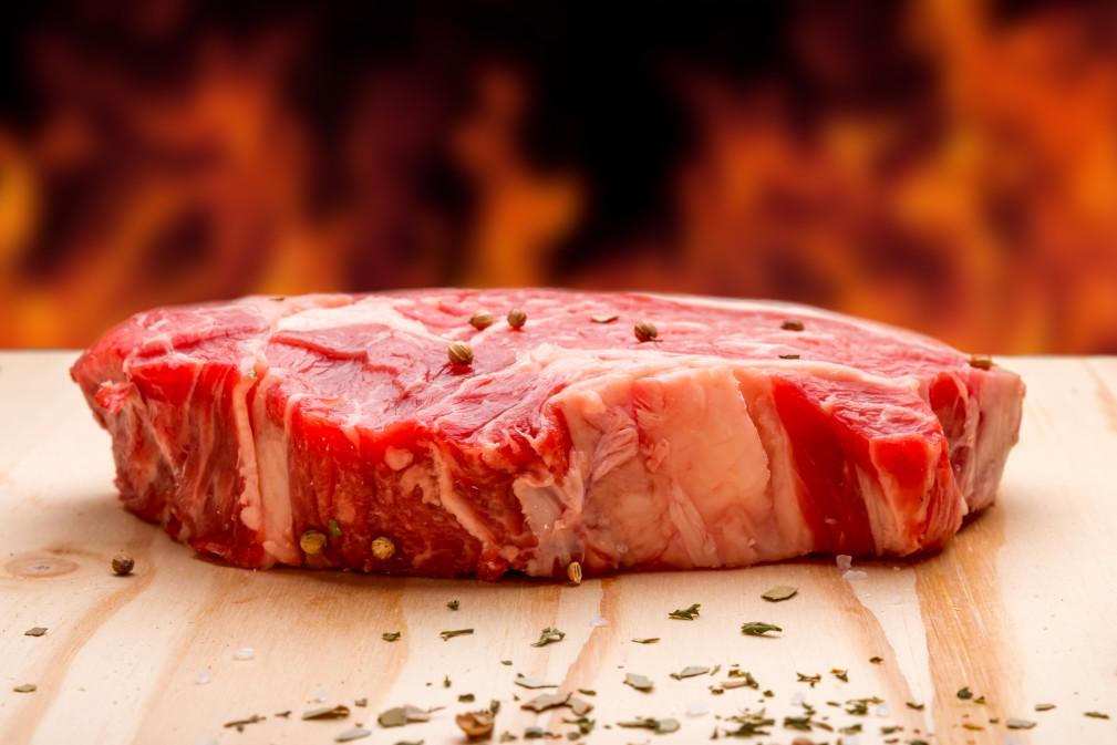fresh-raw-beef-rib-eye-steak-ready-for-grill-with-seasoning-and-background-fire_t20_3erb9y